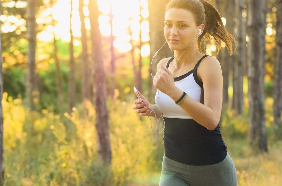 A woman jogging in nature and wearing headphones